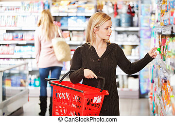 Shopping Woman - Young woman carrying basket while shopping...