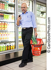 Man with Grocery Basket and Mobile Phone - Man with shopping...