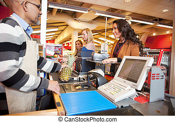 Grocer Store Checkout - Shop assistant with customer in...