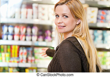 Portrait of Woman in Supermarket - Close-up of smiling woman...