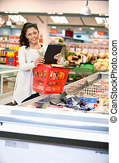 Woman with Electronic Shopping List - Shopper with basket...
