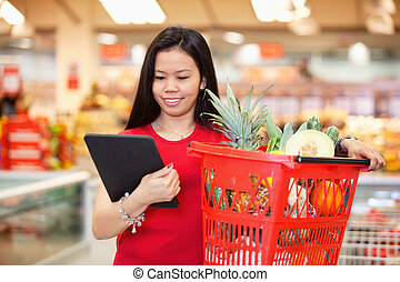 Woman looking at digital tablet - Smiling woman looking at...