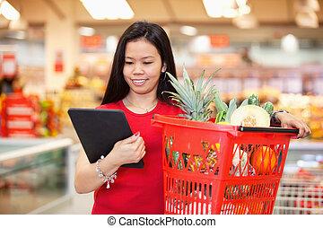 Woman looking at digital tablet - Smiling woman looking at...