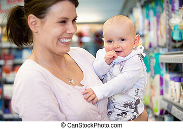 Cheerful mother and baby in shopping centre - Close-up of...