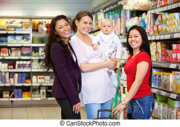 Happy Friends in Grocery Store - Woman holding baby and...