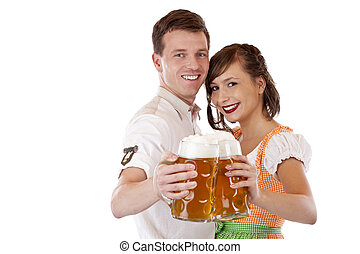 Happy Bavarian man and woman in dirndl with oktoberfest beer stein. Isolated on white background.