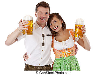 Bavarian man and woman in dirndl and lederhose with beer stein