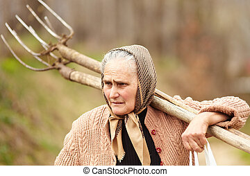 Senior farmer woman with a fork - Old farmer woman carrying...