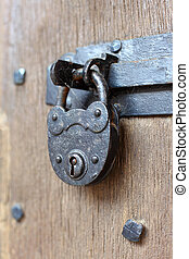Ancient padlock at a wooden door