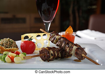 Kebab tomatoe and red wine - Kebab on a white dish with a...
