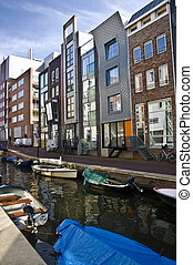 Modern residential houses on the canal in Amsterdam. Spring cityscape.