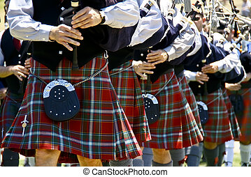 Bagpipe players in line at a parade.