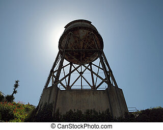 Looking up at Rusted out Water Tower on Alcatraz Island with sun directly behind it, and vines beginning to grow up the side of the foundation.