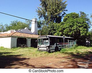 Broken down bus rests next to a rundown chapel in San Juan,...