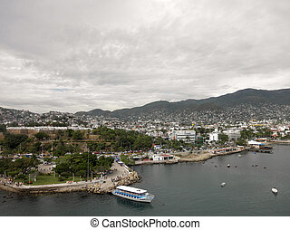Shoreline and cityscape of Acapulco during a cloudy day with...