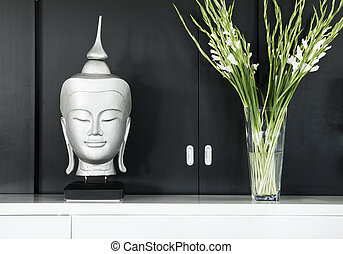 contemporary interior design detail with buddha image and flowers