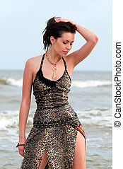 woman in a dress standing on the beach