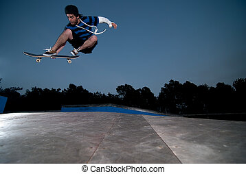 Skateboarder on a ollie at night at the local skatepark.