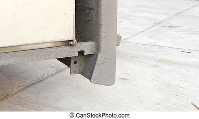Lowering the ramp of a trailer - Man, manually lowering the...