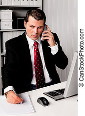 Businessman in office with telephone - Young businessman in...