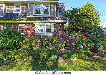 Brick old cute house with green summer landscape