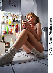 sweet desire - Woman sitting in front of a fridge at...