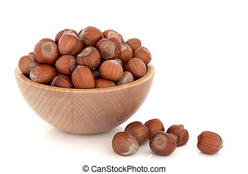 Hazelnuts in a beech wood bowl and loose isolated over white...