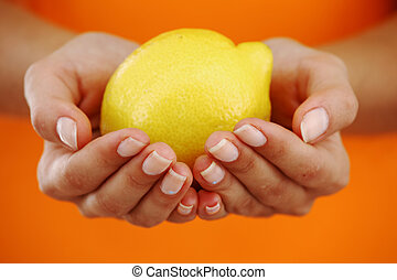 lemon in woman hands close up