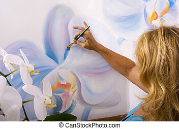 female artist painting phalaenopsis orchids on canvas in her...