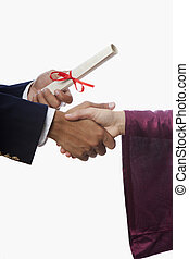 handshake and a diploma at graduation