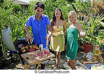 three friends having a barbecue lunch in their tropical...