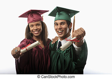 multi racial couple in cap and gown with diploma at...