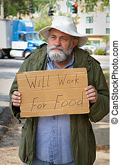 Begging With Sign - Homeless veteran begging at the side of...