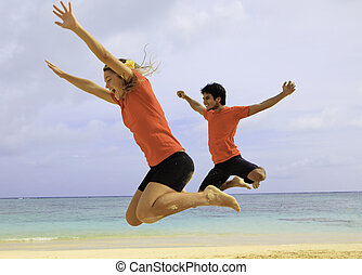 couple jumping in the air at a hawaii beach