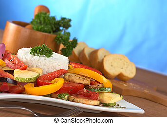 Ratatouille of zucchini, eggplant, tomato, bell pepper and onion with cooked rice and mortar with herbs and baguette in the back (Selective Focus, Focus on the front of the rice, the parsley on top an