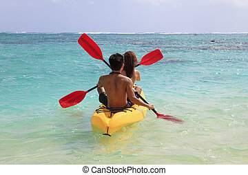 young couple kayaking in hawaii