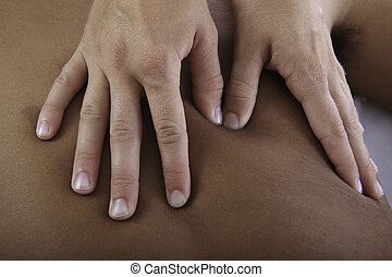 healing touch of a masseus's hands as she massages a young...