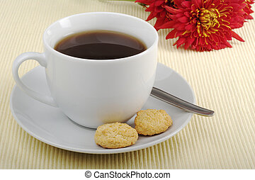Black tea in cup with saucer, teaspoon, biscuits and flower...