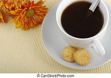 Blacktea in cup with saucer, teaspoon, biscuits and orange...