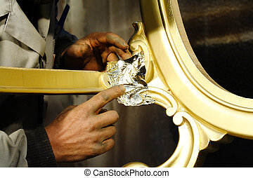 Hands working on wood gilding - Hands working on wood with...