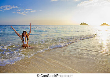 young woman at the beach at sunrise - beautiful young woman...