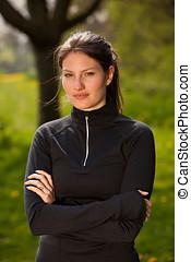 Sporty girl in sportswear standing outside