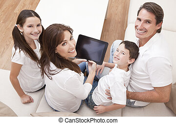 Happy Family Having Fun Using Tablet Computer At Home - An...