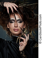 High fashion model in black dress, with long nails, creative...