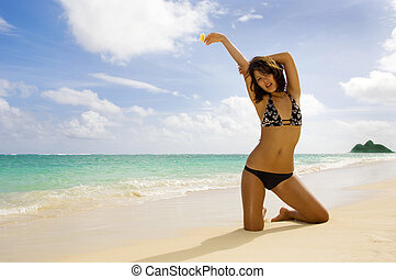 beautiful young woman in a bikini at a tropical beach in...