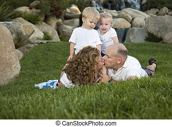 Affectionate Couple Kiss as Cute Twins Look On