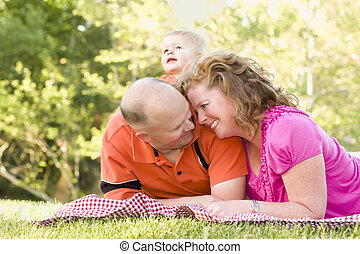 Affectionate Couple with Son in Park - Affectionate Couple...