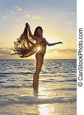 beautiful black female dancer standing in the ocean at...