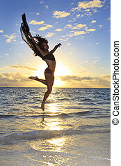 beautiful black female dancer leaping in the air over the...