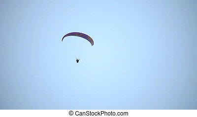 Paraplane - paraglider glide and down against the sky